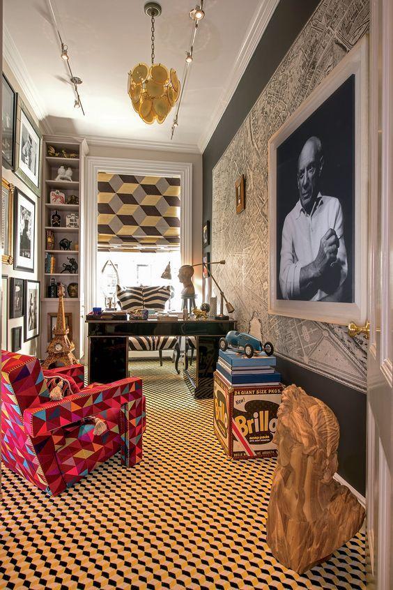 un bureau à domicile maximaliste dynamique avec une carte et une œuvre d'art audacieuse sur le mur, un mur de galerie, un sol géométrique et un rideau imprimé