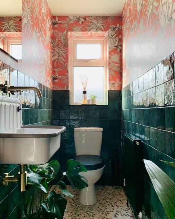 une salle de bain maximaliste audacieuse avec du papier peint à fleurs rouges, des carreaux vert foncé, des touches de laiton de plantes remarquables