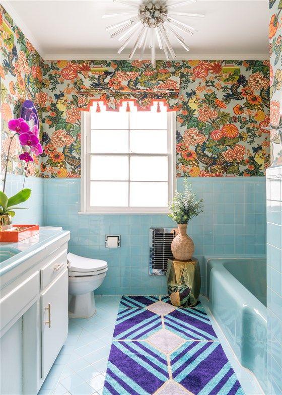 une salle de bain maximaliste lumineuse avec des carreaux bleus et une baignoire, un papier peint fleuri brillant, des fleurs audacieuses et un lustre sunbrust