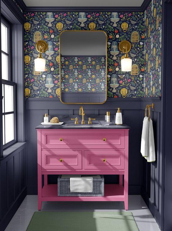 une salle de bain maximaliste audacieuse avec des lambris gris graphite, du papier peint floral foncé, une vanité rose vif et des touches dorées
