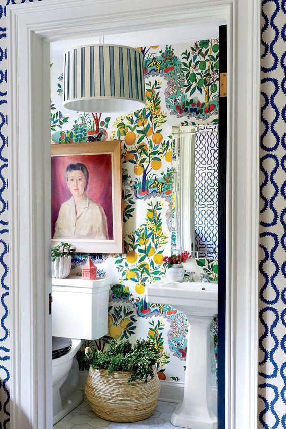 une salle de bain maximaliste audacieuse avec du papier peint à imprimé de fruits, une lampe à rayures, de la verdure en pot, une œuvre d'art audacieuse et des appareils d'inspiration vintage
