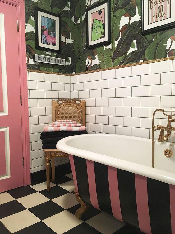 une salle de bain lumineuse avec des carreaux de métro blancs, du papier peint à feuilles tropicales, une baignoire à rayures, une porte rose et un sol à carreaux ainsi que des œuvres d'art pop