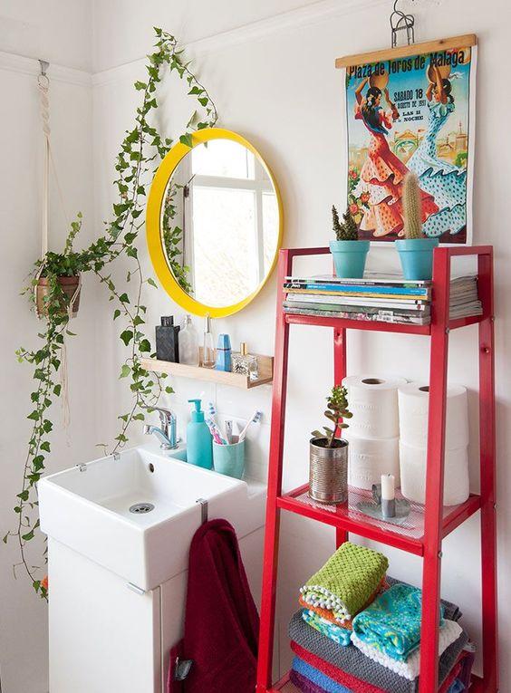 une salle de bain maximaliste avec un miroir à cadre jaune, une échelle rouge avec un décor et une œuvre d'art colorée ainsi que de la verdure en pot