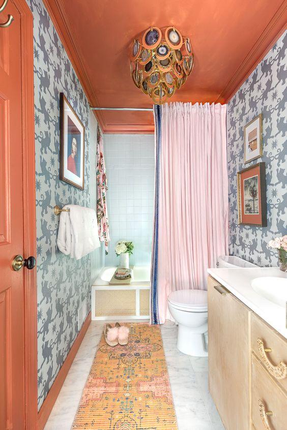 une salle de bain maximaliste colorée avec des murs imprimés en gris, un plafond rouille et une porte, un tapis audacieux, un lustre en agate créatif et un rideau rose