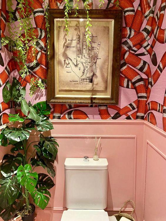une salle de bain maximaliste colorée avec des panneaux roses, du papier peint à imprimé serpent, des plantes en pot et une œuvre d'art audacieuse est créative