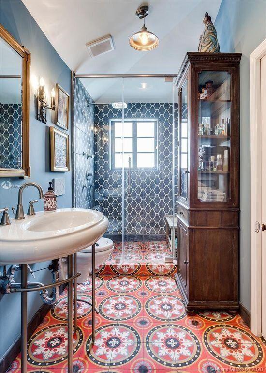 une salle de bain maximaliste avec des murs bleus et des carreaux bleus, un sol en mosaïque rouge, un meuble de rangement teinté et un petit mur de galerie