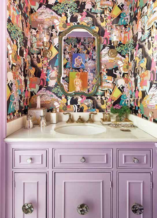 une salle de bain maximaliste avec du papier peint follement imprimé, une vanité intégrée lilas et un miroir dans un cadre vintage est chic
