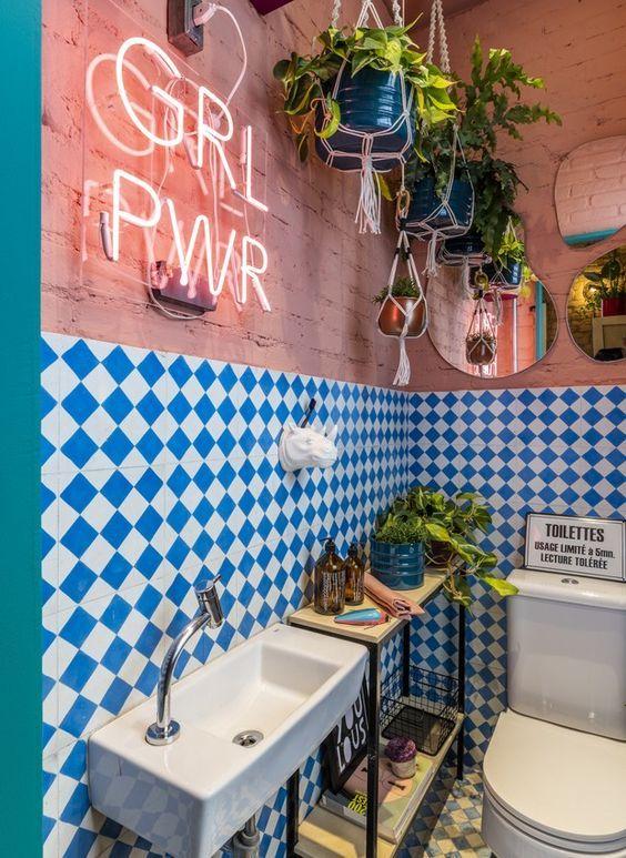 une salle de bain maximaliste avec des murs en briques roses, des carreaux à carreaux bleus et blancs, une console, de la verdure en pot, une enseigne au néon et des miroirs