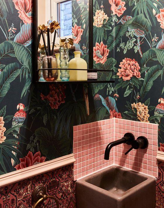 une salle de bain maximaliste avec du papier peint floral dakr, des carreaux roses, un lavabo rose, des luminaires noirs et une étagère noire