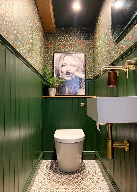 une salle de bain maximaliste avec du papier peint à fleurs, des panneaux verts, une œuvre d'art et une œuvre d'art et des touches de laiton