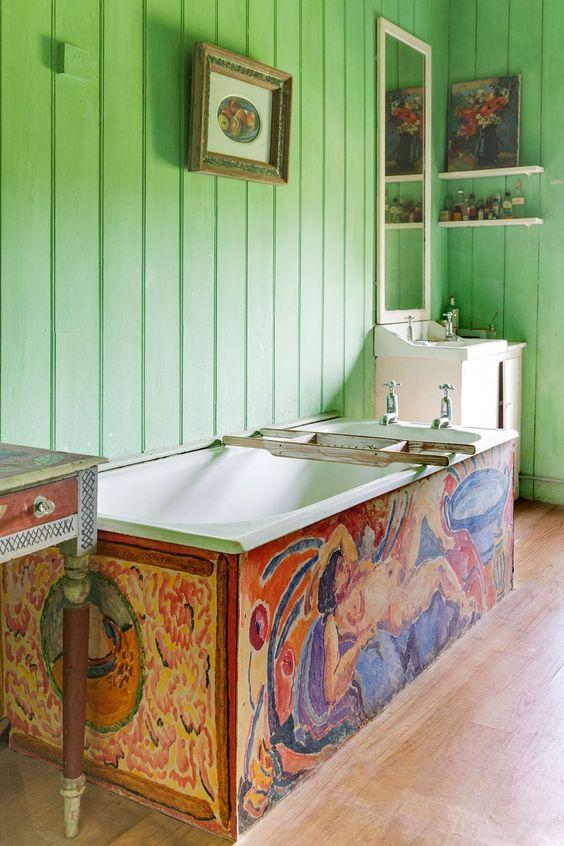 une salle de bain maximaliste avec des murs en planches vertes, une baignoire colorée, un meuble lavabo peint, de jolies œuvres d'art et chic