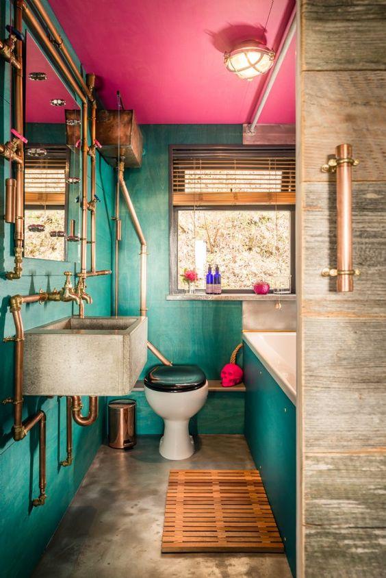 une salle de bain maximaliste avec des murs verts et un plafond rose vif, un sol en béton et un lavabo, des tuyaux exposés en cuivre et un crâne