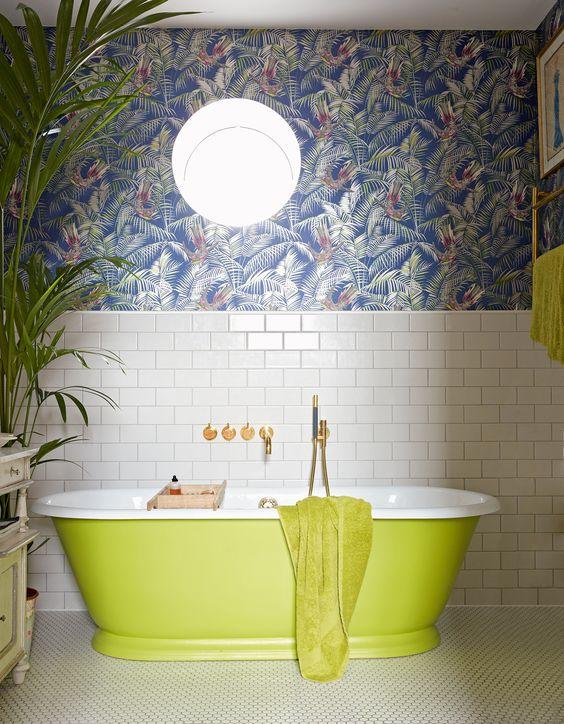 une salle de bain maximaliste avec des carreaux de métro blancs, du papier peint à feuilles tropicales sombres, une baignoire et des serviettes vert néon, une plante remarquable