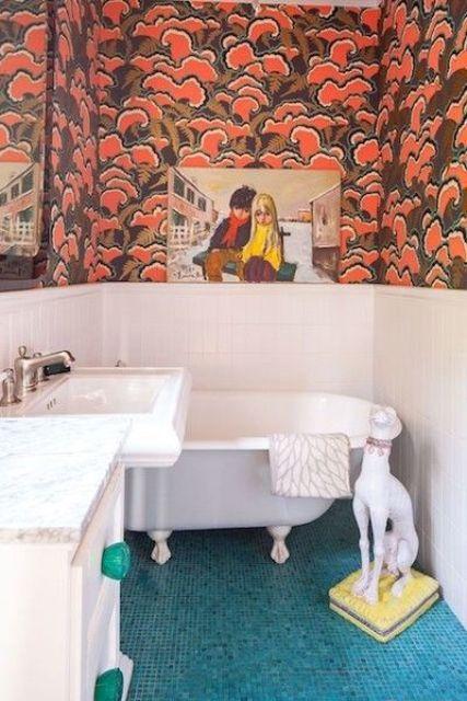 une salle de bain maximaliste avec des lambris blancs et du papier peint imprimé audacieux, des carreaux bleus au sol, des œuvres d'art et un chien