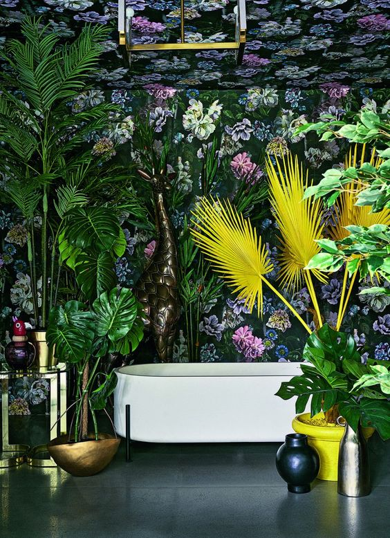 un espace maximaliste avec du papier peint floral foncé, des plantes audacieuses en vert et jaune, des touches de laiton et des vases