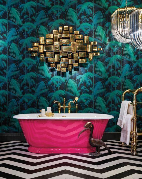 une salle de bain maximaliste raffinée avec un mur d'accent tropical, une baignoire rose vif, une œuvre d'art en or, des lustres chics et un sol en chervon noir et blanc