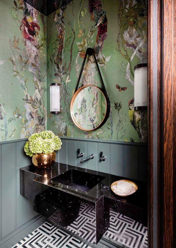 une salle de bain maximaliste raffinée avec du papier peint flore et faune verte, une vanité en pierre noire, un sol en mosaïque et un miroir rond
