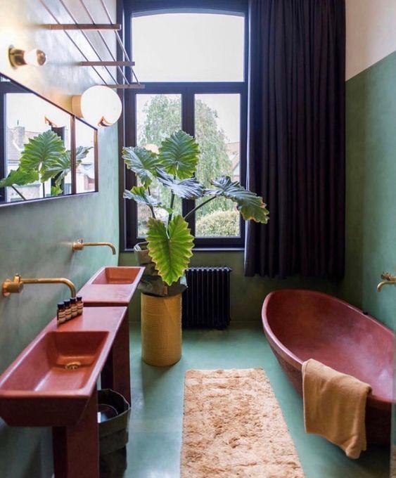 une salle de bain vibrante avec des murs et un sol de couleur aqua, des lavabos roses et une baignoire, des luminaires dorés et un rideau noir