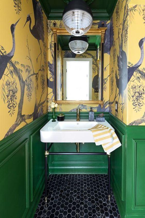 une salle de bain vintage maximaliste avec des murs en papier peint aux oiseaux jaunes, des lambris verts, un sol en carrelage hexagonal noir, un miroir dans un cadre doré et une lampe