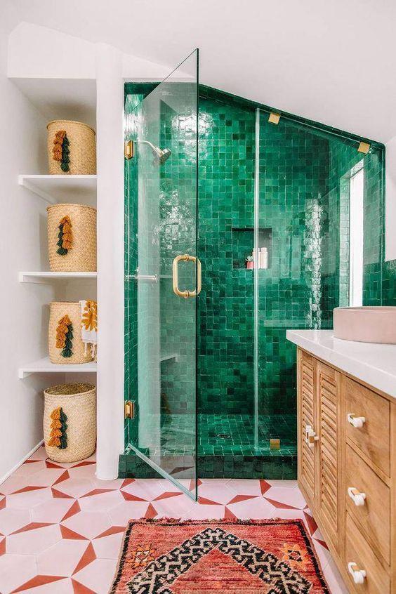 une salle de bain maximaliste vibrante avec un sol en carrelage rose et rouge, un espace de douche en carrelage vert, un tapis rouge et des paniers à pompons