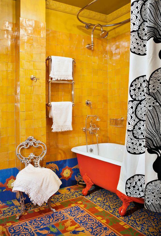 une salle de bain maximaliste super audacieuse avec des carreaux jaunes et bleus audacieux, des carreaux de mosaïque colorés au sol, une baignoire rouge, une chaise vintage