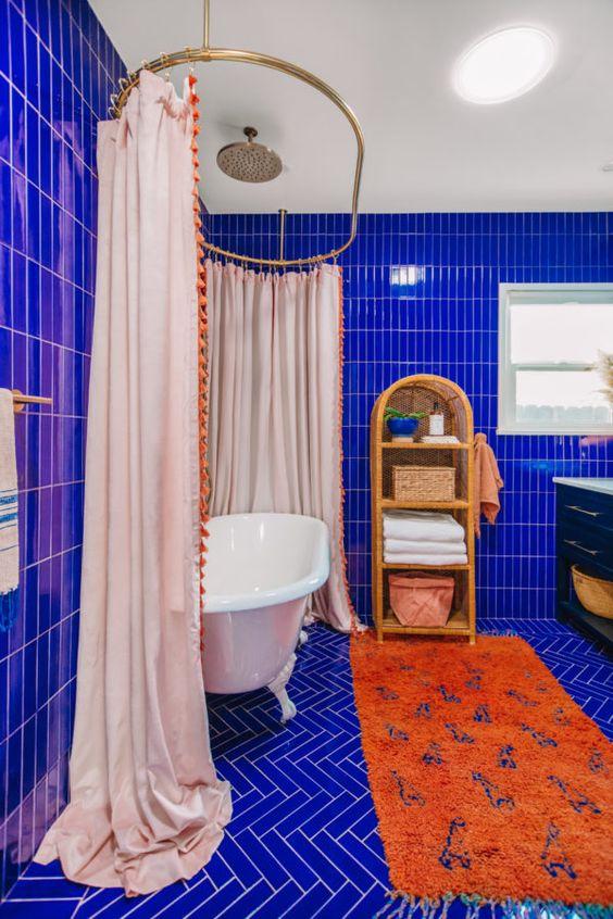 une salle de bain maximaliste super vibrante revêtue de carreaux bleu électrique, une baignoire vintage avec un grand rideau, un tapis orange, une étagère en rotin et une vanité noire