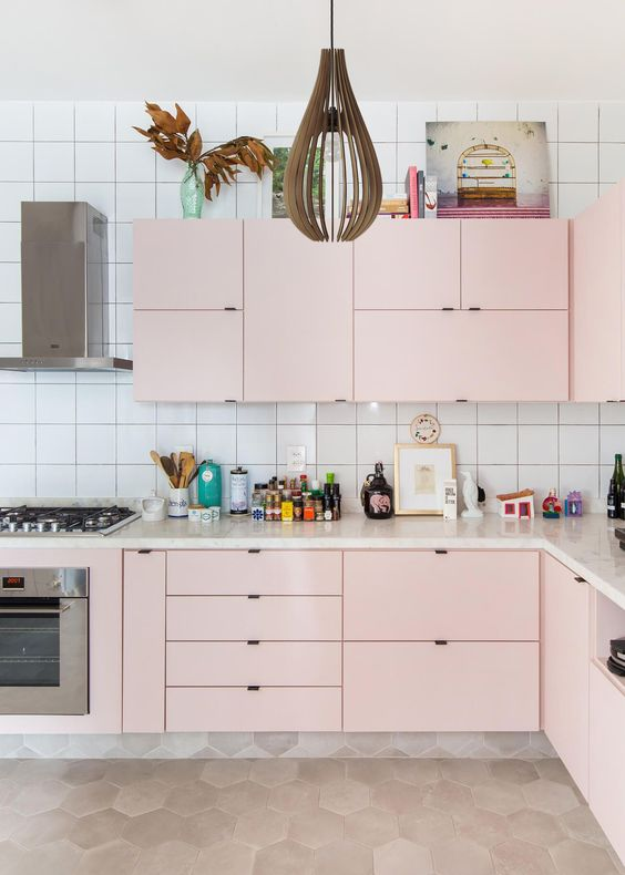 une cuisine pastel moderne réalisée en rose tendre, avec une suspension accrocheuse et un dosseret en carreaux carrés blancs