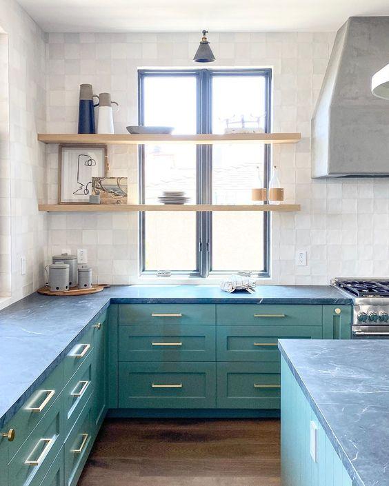 une nuance inhabituelle de vert et des comptoirs en pierre grise donnent à la cuisine un aspect inhabituel et très audacieux