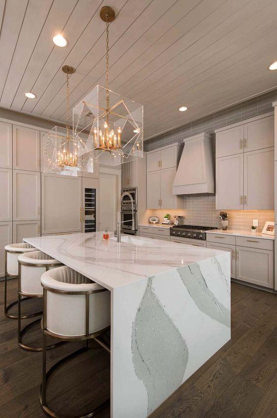 une cuisine raffinée de couleur neutre avec un îlot de cuisine à couper le souffle avec un comptoir en cascade et de superbes lustres en or et en verre transparent