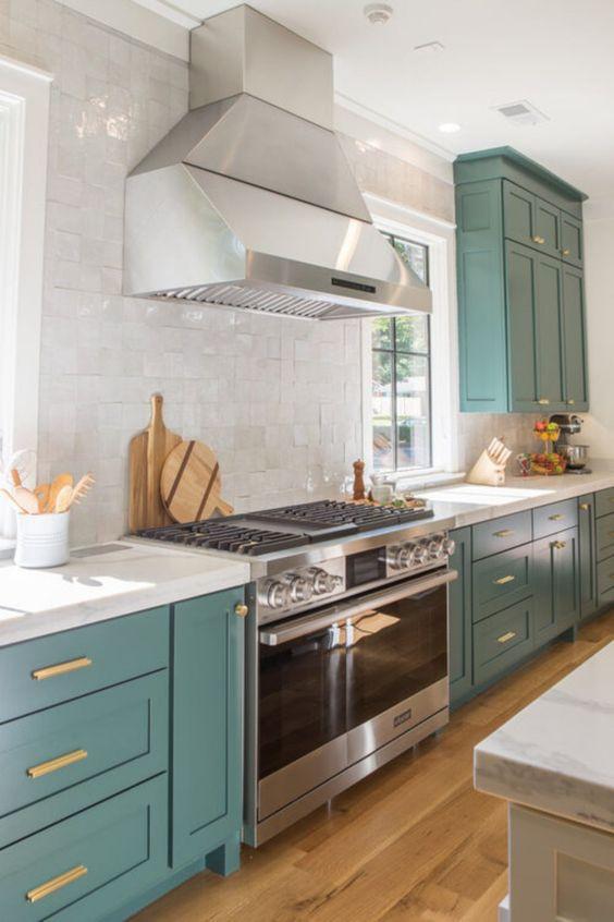 une belle cuisine sarcelle avec des comptoirs en pierre blanche et un dosseret en carreaux blancs et des touches d'or semblent audacieuses