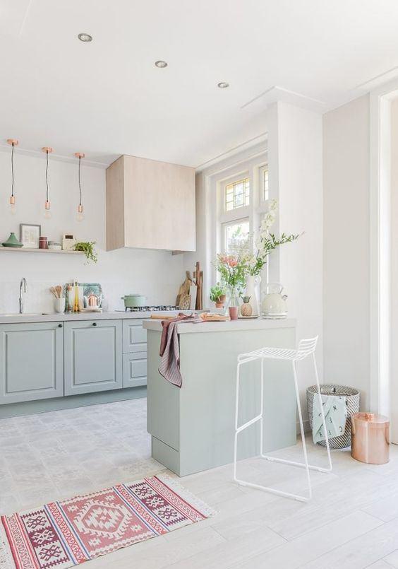 une belle cuisine pastel avec des armoires vert menthe, des touches de rose, de cuivre et un tapis géométrique met en valeur un combo de couleurs froides