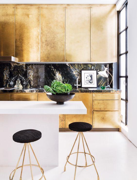 une cuisine dorée avec un dosseret en pierre noire et un comptoir plus un îlot de cuisine minimaliste blanc pour un look à couper le souffle