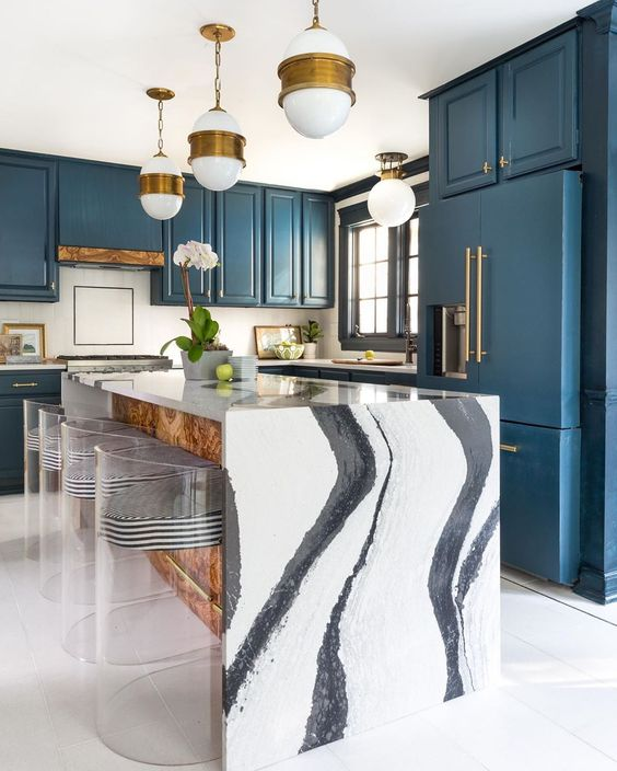 une cuisine marine avec des poignées en laiton et des suspensions, un fantastique îlot de cuisine cascade en noir et blanc et des tabourets rayés