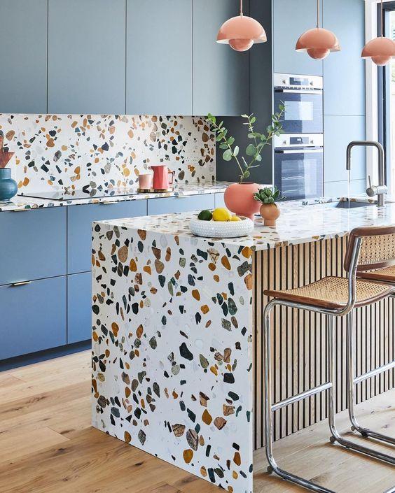 une cuisine lumineuse avec des armoires bleues, des comptoirs en terrazzo, un dosseret et un îlot de cuisine et des touches de corail est incroyable
