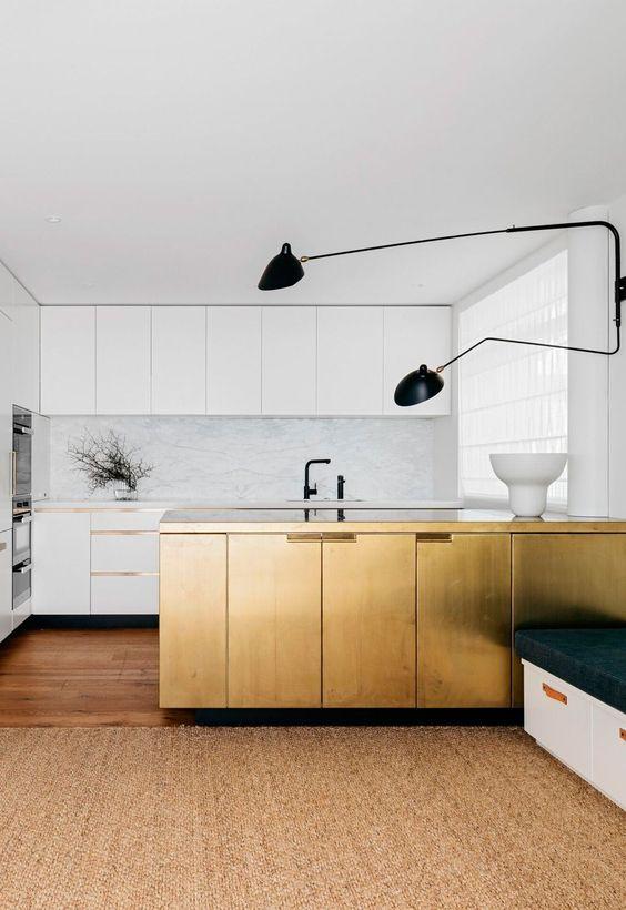 une cuisine minimaliste blanche avec un dosseret et des comptoirs en pierre blanche, des luminaires noirs et un îlot de cuisine doré pour une déclaration