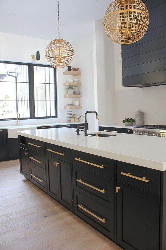 une cuisine contrastante gris graphite et blanc avec des poignées dorées et des lampes suspendues globe dorées assorties a l'air chic