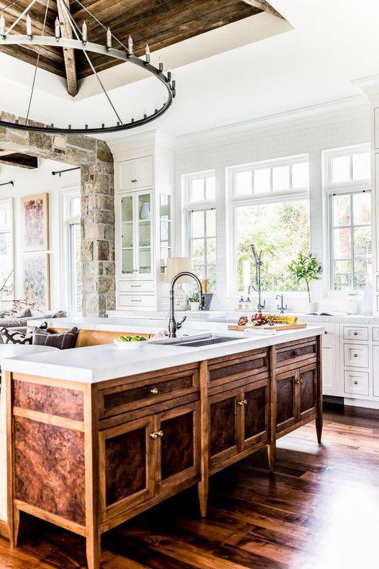 une cuisine blanche de ferme avec un îlot de cuisine en bois richement teinté d'époque unique et un grand lustre en métal a l'air wow