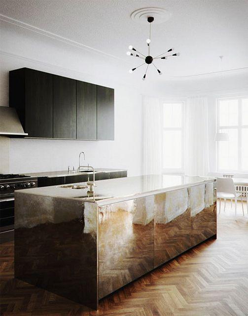 une cuisine noire minimale avec un îlot de cuisine en métal brillant qui apporte une touche glamour à l'espace et le fait ressortir beaucoup