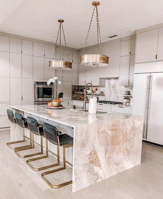 une élégante cuisine gris tourterelle avec un îlot de cuisine en pierre rose, des tabourets fantaisie noirs et dorés et des suspensions dorées