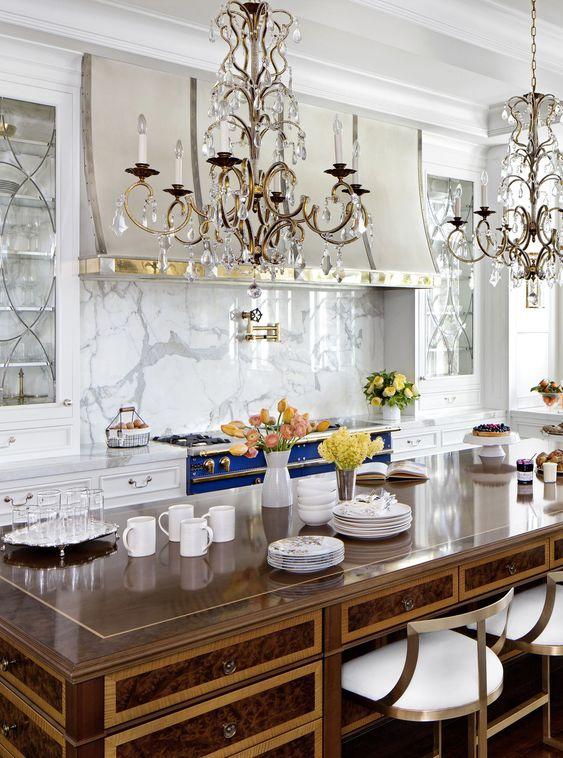 une cuisine raffinée d'inspiration vintage en blanc, avec une cuisinière bleue audacieuse, un dosseret en marbre blanc, des lustres en cristal et un bureau vintage comme îlot de cuisine