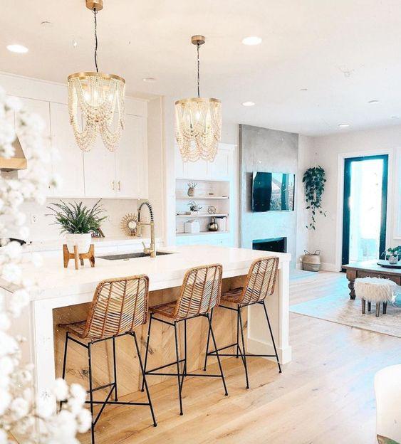 incroyables lustres en perles de bois, les tabourets en rotin rendent cette cuisine blanche glamour, chic et très exceptionnelle