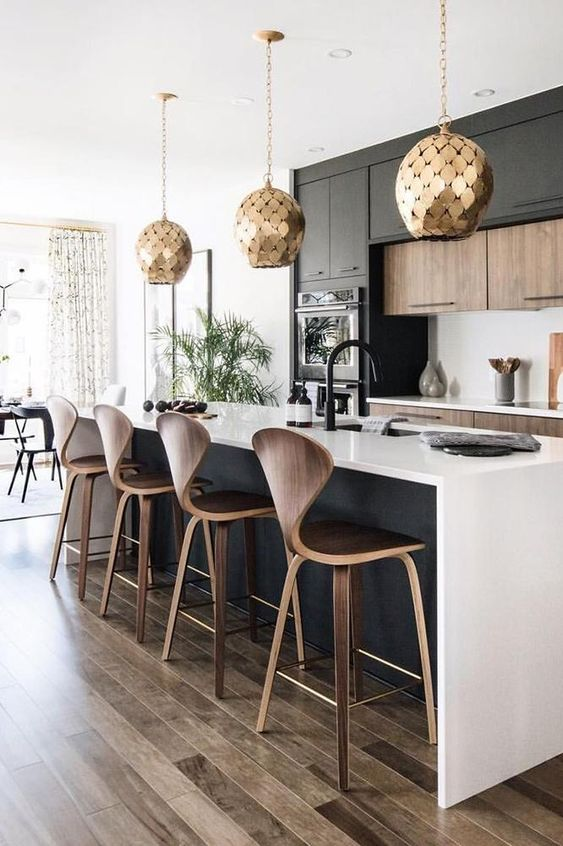 une élégante cuisine contemporaine en noir et blanc avec des lampes suspendues à l'échelle d'or à couper le souffle est à couper le souffle