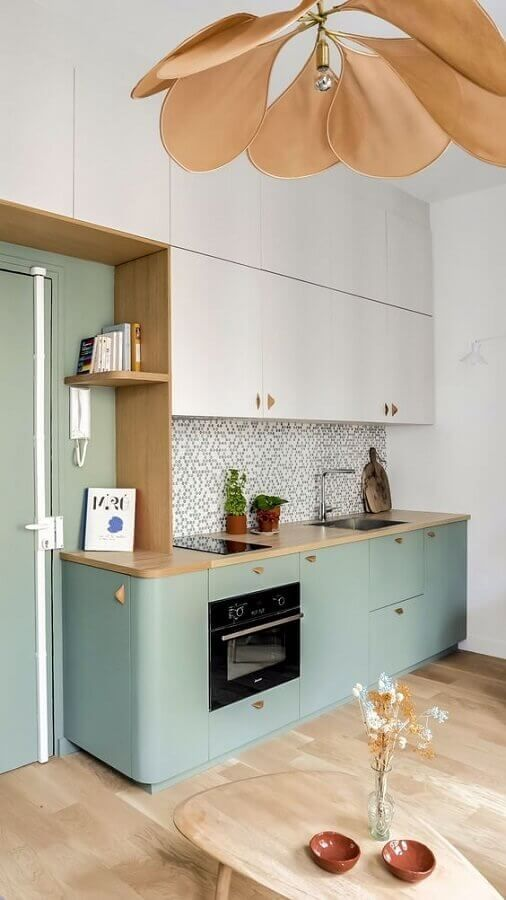 une combinaison de couleurs élégantes de gris tourterelle et de vert, avec des comptoirs en bois teintés et un lustre à pétales en cuir
