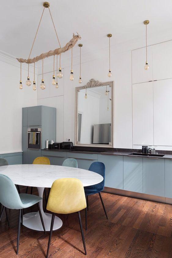 des ampoules suspendues et un lustre en bois flotté avec des ampoules assorties et des armoires bleues pour un look de cuisine côtière absolument innovant