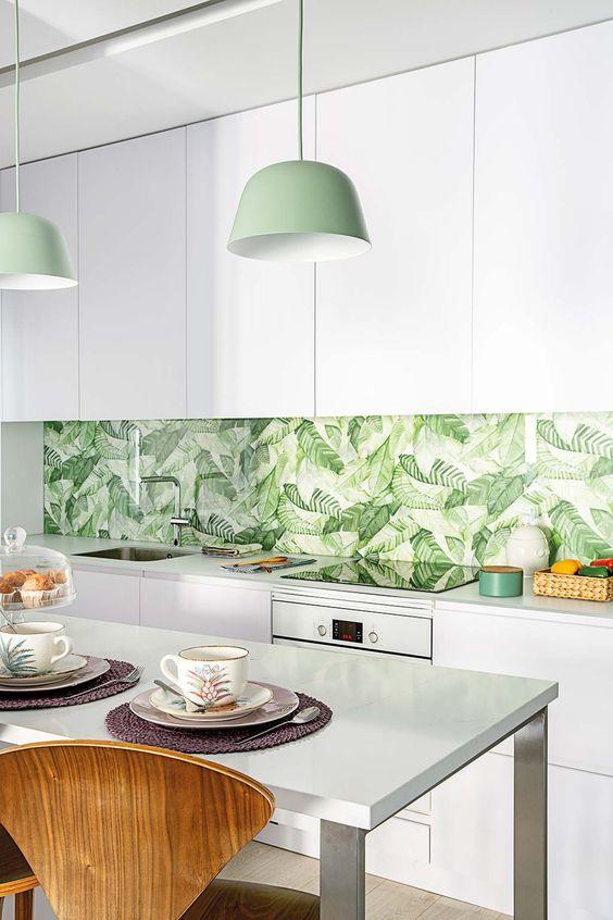 une cuisine blanche minimaliste avec un dosseret de feuilles tropicales, des suspensions vertes et des touches de vert ici et là