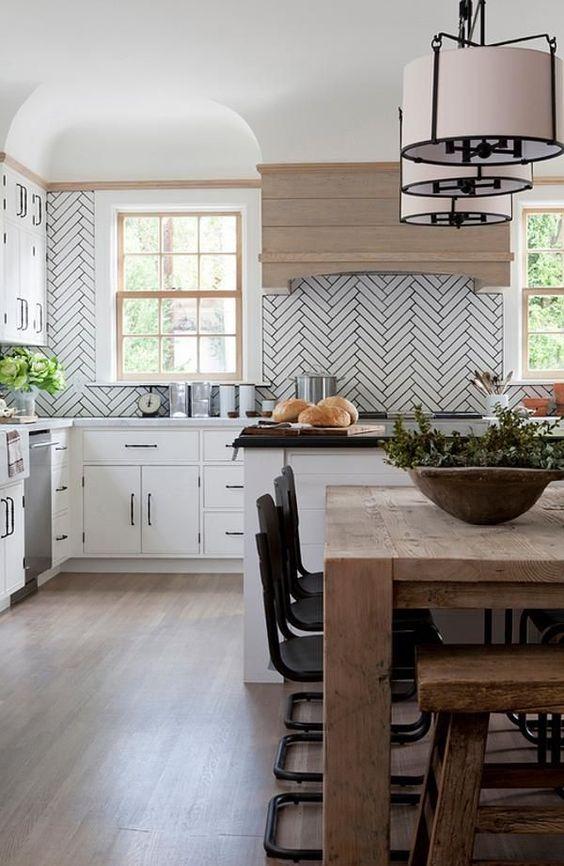 une cuisine blanche rehaussée de longs carreaux blancs et de coulis gris ainsi qu'une hotte en bois teintée pour plus de confort