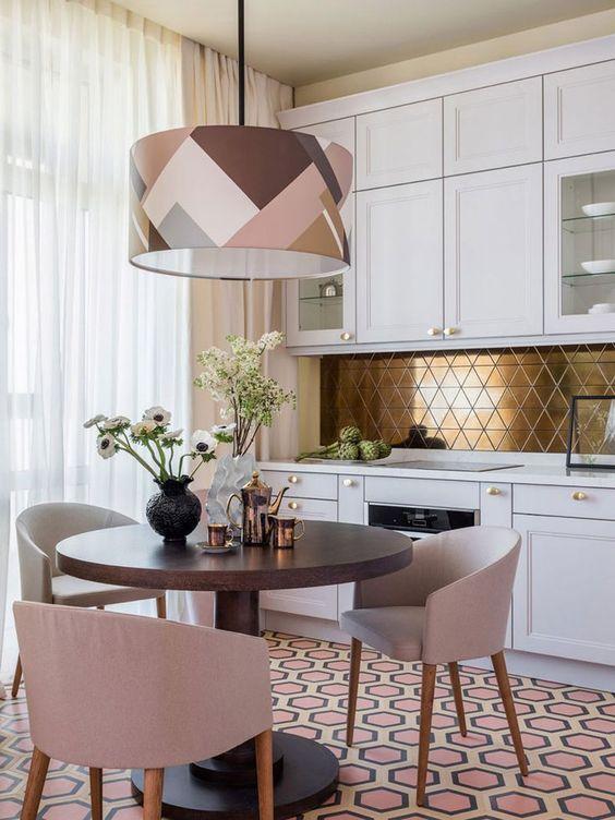 une cuisine glam moderne en blanc, avec un dosseret géométrique doré et une suspension géométrique accrocheuse à bascule