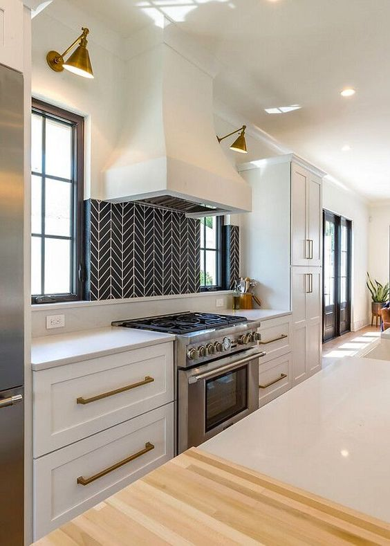 une cuisine blanche chic avec des poignées en laiton, des appliques murales et un dosseret de carreaux géométriques noirs et blancs