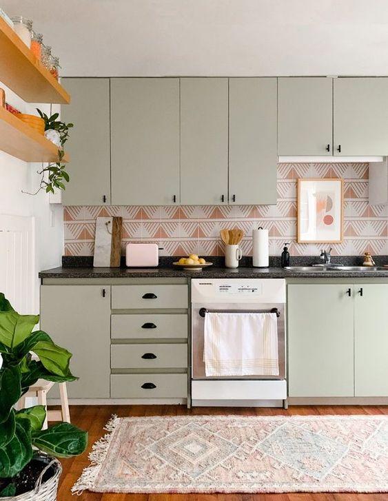 une cuisine vert olive avec des poignées noires et un dosseret à imprimé géométrique rouille et blanc très accrocheur qui se démarque