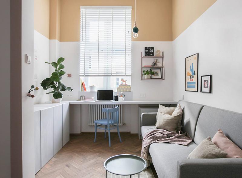 Le salon dispose d'un canapé, d'une table et d'un espace de travail confortable sur le rebord de la fenêtre, les murs en blocs de couleur rendent la pièce accrocheuse et gaie